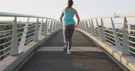 handrails : Rear view of a fit Caucasian woman with long dark hair wearing sportswear, exercising outdoors in the city, running through the bridge in slow motion.