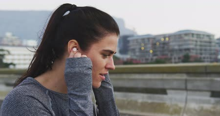 listening music : Side view close up of a fit Caucasian woman with long dark hair wearing sportswear, exercising outdoors in the city, listening to music on earphones, taking break standing in the street, putting on her headphones in slow motion.