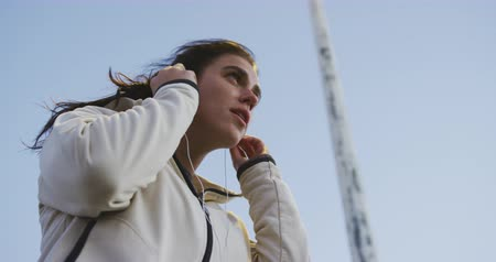 listening music : Front low angle view close up of a fit Caucasian woman with long dark hair wearing sportswear, exercising outdoors in the city, listening to music on earphones, taking break standing in the street, putting on her headphones in slow motion.