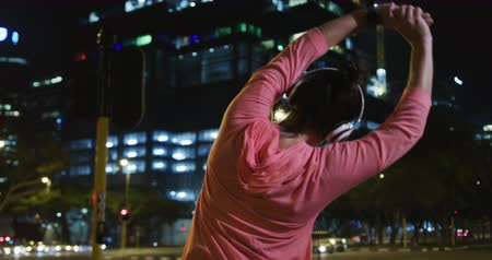 trecho : Rear view of a fit Caucasian woman with long dark hair wearing sportswear, exercising outdoors in the city during night, wearing headphones, warming up, stretching her arms and starting to run.