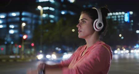 listening music : Side view close up of a fit Caucasian woman with long dark hair wearing sportswear, exercising outdoors in the city during night, wearing headphones, warming up, stretching her arms and starting to run.