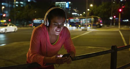 corrimão : Front view of a fit Caucasian woman with long dark hair wearing sportswear, exercising outdoors in the city during night, wearing headphones, resting leaning against a handrail, smiling and using her smartphone. Vídeos