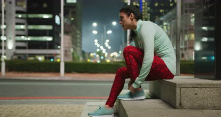 koronka : Side view of a fit Caucasian woman with long dark hair wearing sportswear, exercising outdoors in the city during the night, sitting on a step in the street, tying her shoes and starts to run.