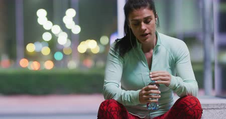 listening music : Front view of a fit Caucasian woman with long dark hair wearing sportswear, exercising outdoors in the city, listening to music on earphones, taking break sitting on a step in the street, drinking water and wiping her brow.