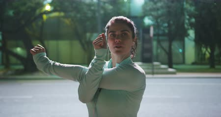 listening music : Front view close up of a fit Caucasian woman with long dark hair wearing sportswear, exercising outdoors in the city during night, wearing headphones, warming up, stretching her arms.