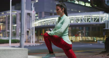 listening music : Side view of a fit Caucasian woman with long dark hair wearing sportswear, exercising outdoors in the city during night, wearing headphones, warming up, stretching her legs.