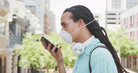 individualidade : Side view of a mixed race man with long dreadlocks out and about in the city on a sunny day, standing in the street wearing a coronavirus mask and using a smartphone in slow motion. Stock Footage