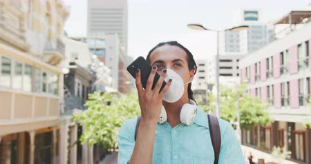 içerik : Front view of a mixed race man with long dreadlocks out and about in the city on a sunny day, standing in the street wearing a coronavirus mask and using a smartphone in slow motion.