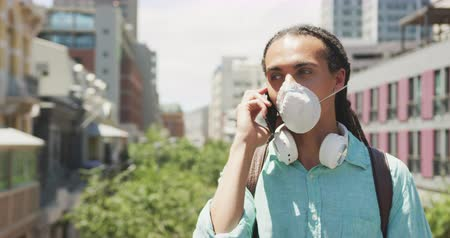 koróna : Front view of a mixed race man with long dreadlocks out and about in the city on a sunny day, standing in the street wearing a coronavirus mask and using a smartphone in slow motion.
