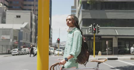 ciclismo : Side view of a mixed race man with long dreadlocks out and about in the city on a sunny day, wearing backpack, walking the street and wheeling his bicycle in slow motion.
