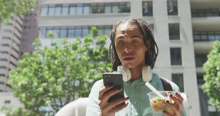 individualidade : Front view of a mixed race man with long dreadlocks out and about in the city on a sunny day, standing in the street, using his smartphone and smiling, holding a bowl of a salad.