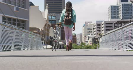 individualidade : Rear view of a mixed race man with long dreadlocks out and about in the city on a sunny day, wearing backpack, walking the street and wheeling his bicycle in slow motion. Stock Footage