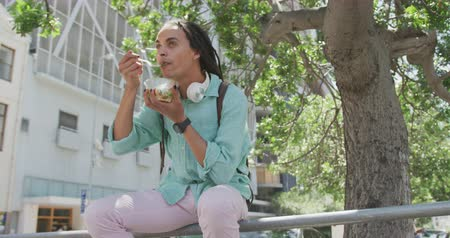 individualidade : Front low angle view of a mixed race man with long dreadlocks out and about in the city on a sunny day, sitting in the street, holding a bowl of a salad and eating in slow motion.