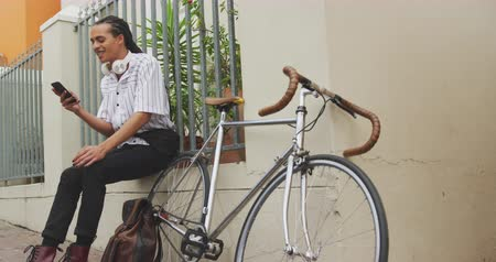 ciclismo : Side view of a mixed race man with long dreadlocks out and about in the city on a sunny day, sitting in the street and smiling, using a smartphone, with his bicycle leaning against the wall next to him in slow motion. Stock Footage