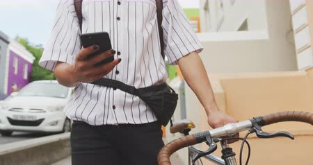 ciclismo : Front view mid section of a mixed race man with long dreadlocks out and about in the city on a sunny day, using his smartphone, walking the street and wheeling his bicycle in slow motion. Stock Footage