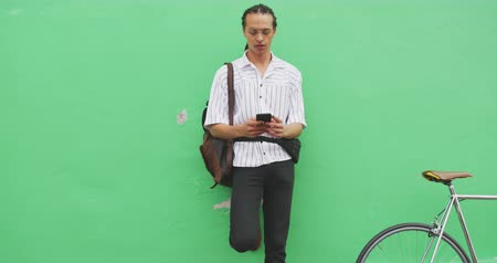 individualidade : Front view of a mixed race man with long dreadlocks out and about in the city on a sunny day, standing in the street, using a smartphone, with his bicycle leaning against the wall next to him in slow motion. Stock Footage