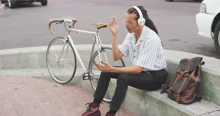 ileri : Side view of a mixed race man with long dreadlocks out and about in the city on a sunny day, sitting in the street, wearing headphones, using a smartphone, with his bicycle standing next to him in slow motion.
