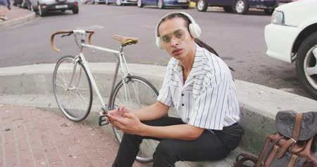 ciclismo : Side view of a mixed race man with long dreadlocks out and about in the city on a sunny day, sitting in the street, wearing headphones, using a smartphone, looking straight into camera, with his bicycle standing next to him in slow motion. Stock Footage