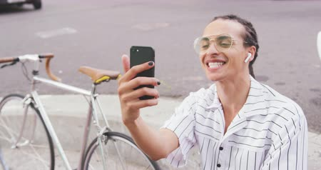 individualidade : Front view close up of a mixed race man with long dreadlocks out and about in the city on a sunny day, sitting in the street, wearing headphones, using a smartphone, waving his hand, with his bicycle standing next to him in slow motion. Stock Footage
