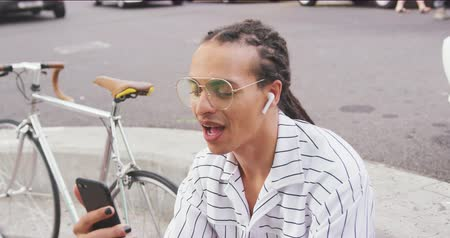 ciclismo : Front view close up of a mixed race man with long dreadlocks out and about in the city on a sunny day, sitting in the street, wearing headphones, using a smartphone, waving his hand, with his bicycle standing next to him in slow motion. Stock Footage