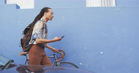 ciclismo : Side view of a mixed race man with long dreadlocks out and about in the city on a sunny day, using his smartphone, walking the street and wheeling his bicycle in slow motion. Stock Footage