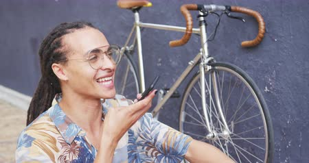 ciclismo : Front view close up of a mixed race man with long dreadlocks out and about in the city on a sunny day, sitting in the street, holding a cup of coffee, using a smartphone, with his bicycle leaning against the wall next to him in slow motion.