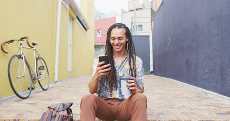 individualidade : Front view of a mixed race man with long dreadlocks out and about in the city on a sunny day, sitting in the street, drinking coffee, taking a selfie with his smartphone, with his bicycle leaning against the wall next to him in slow motion.