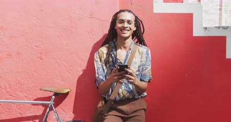 ciclismo : Front view of a mixed race man with long dreadlocks out and about in the city on a sunny day, standing on the street and smiling looking straight into camera, using a smartphone, with his bicycle leaning against the wall next to him in slow motion.