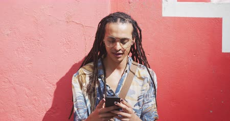 sobre : Front view close up of a mixed race man with long dreadlocks out and about in the city on a sunny day, standing in the street and smiling, using a smartphone in slow motion.