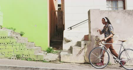 ciclismo : Side view of a mixed race man with long dreadlocks out and about in the city on a sunny day, wearing headphones, walking the street and wheeling his bicycle in slow motion. Stock Footage