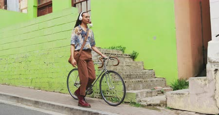 独立記念日 : Front view of a mixed race man with long dreadlocks out and about in the city on a sunny day, wearing headphones, walking the street and wheeling his bicycle in slow motion.