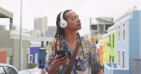 listening music : Front view close up of a mixed race man with long dreadlocks out and about in the city on a sunny day, wearing headphones, standing in the street, using a smartphone in slow motion.