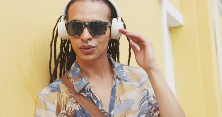 independence : Front view close up of a mixed race man with long dreadlocks out and about in the city on a sunny day, wearing headphones and sunglasses, standing in the street, listening to music in slow motion.