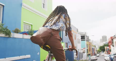 individualidade : Rear view of a mixed race man with long dreadlocks out and about in the city on a sunny day, wearing headphones, riding his bicycle in the street in slow motion.