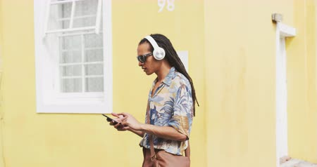listening music : Side view of a mixed race man with long dreadlocks out and about in the city on a sunny day, wearing headphones and sunglasses, walking the street, using a smartphone in slow motion. Stock Footage