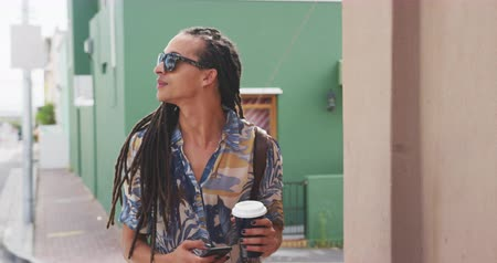 individualidade : Front view close up of a mixed race man with long dreadlocks out and about in the city on a sunny day, wearing sunglasses, walking the street, holding a cup of coffee, using a smartphone in slow motion. Stock Footage