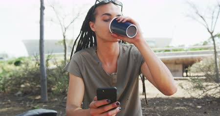 individualidade : Front view of a mixed race man with long dreadlocks out and about in the city on a sunny day, wearing sunglasses, sitting in the street, drinking coffee, using a smartphone in slow motion.