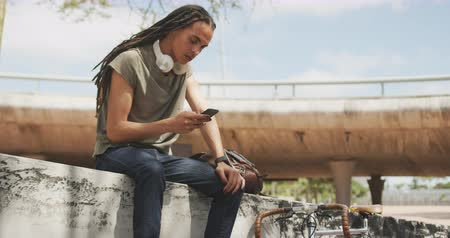 ileri : Side view of a mixed race man with long dreadlocks out and about in the city on a sunny day, sitting on the stairs in the street and smiling, using a smartphone, with his bicycle leaning against the wall next to him in slow motion. Stok Video
