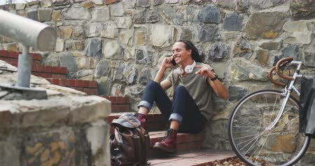 ciclismo : Front view of a mixed race man with long dreadlocks out and about in the city on a sunny day, sitting on the stairs in the street and smiling, using a smartphone, with his bicycle leaning against the wall next to him in slow motion.