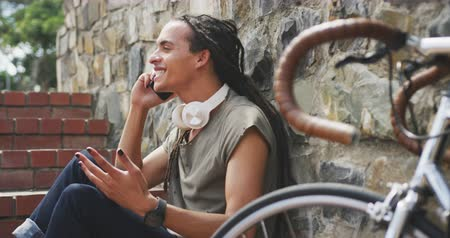 ciclismo : Side view of a mixed race man with long dreadlocks out and about in the city on a sunny day, sitting on the stairs in the street and smiling, using a smartphone, with his bicycle leaning against the wall next to him in slow motion. Stock Footage