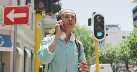 individualidade : Front view close up of a mixed race man with long dreadlocks out and about in the city on a sunny day, standing in the street and rising his hand to stop a taxi, using a smartphone in slow motion. Stock Footage