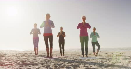 boş zaman : Front view of a group of Caucasian female friends enjoying free time on a beach by the sea on a sunny day together, practicing yoga standing on one leg in slow motion