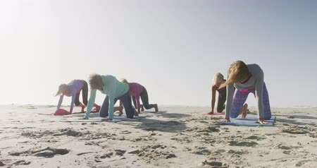 ajoelhado : Front view of a group of Caucasian female friends enjoying free time on a beach by the sea on a sunny day together, practicing yoga kneeling and stretching in slow motion