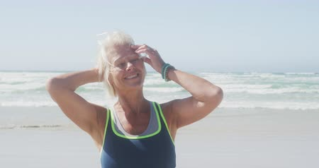 sobressalente : Portrait of a happy senior Caucasian woman enjoying free time on a beach by the sea on a sunny windy day, smiling to camera, swiping her hair from her face in slow motion