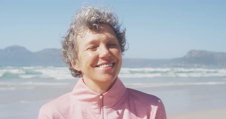 sobressalente : Portrait of a happy senior Caucasian woman enjoying free time on a beach by the sea on a sunny windy day, smiling to camera in slow motion
