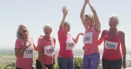 leaping : Fun run race in the sunshine, Front view of a group of Caucasian female friends enjoying free time in countryside on a sunny day together, jumping and celebrating in slow motion Stock Footage