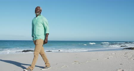 prazer : Side view of a senior African American man walking on the beach with blue sky and sea in the background in slow motion Vídeos