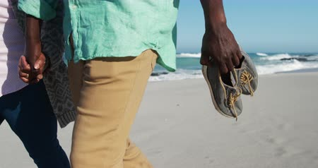 but : Side view of mid section of a senior African American couple enjoying time on the beach with blue sky and sea in the background, holding hands and shoes in slow motion