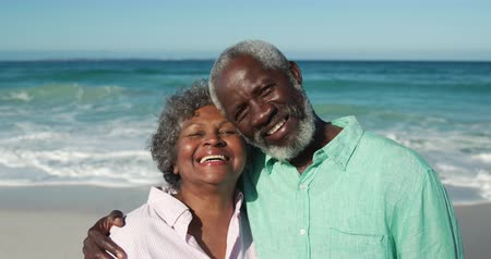 casal : Portrait of a senior African American couple standing on the beach with blue sky and sea in the background, embracing each other, looking at camera and smiling in slow motion Stock Footage