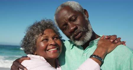 Деятельность выходные : Low angle front view close up of a happy senior African American couple standing on the beach with blue sky in the background, embracing each other and smiling in slow motion